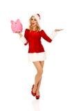 Santa woman holding a piggy bank Stock Photo