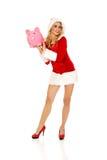 Santa woman holding a piggy bank Stock Image