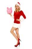 Santa woman holding a piggy bank Royalty Free Stock Images