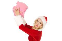 Santa woman holding a piggy bank Royalty Free Stock Photography