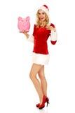 Santa woman holding a piggy bank Royalty Free Stock Image