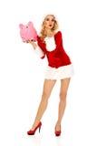 Santa woman holding a piggy bank and sending a kiss Stock Image