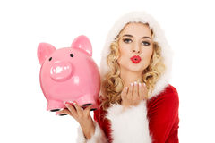 Santa woman holding a piggy bank and sending a kiss Royalty Free Stock Image