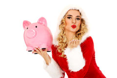 Santa woman holding a piggy bank and sending a kiss Royalty Free Stock Image