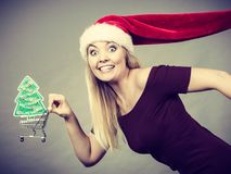 Santa woman holding shopping cart with christmas gifts Royalty Free Stock Image