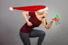 Santa woman holding shopping cart with christmas gifts Stock Photo