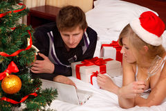 Santa woman lying on bed with her boyfriend Stock Photos