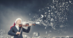 Santa woman play violin Stock Photos
