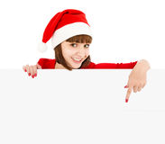 Santa woman pointing on blank sign billboard. Smiling woman in Santa red hat pointing on blank sign billboard, isolated on white Royalty Free Stock Images