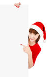 Santa woman pointing on blank sign billboard. Smiling woman in Santa red hat pointing on blank sign billboard, isolated on white Royalty Free Stock Photo