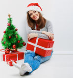 Santa woman seat near Christmas tree with christmas gift. Royalty Free Stock Image