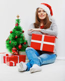 Santa woman seat near Christmas tree with christmas gift. Royalty Free Stock Photo