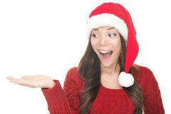 Santa woman showing copyspace excited. Christmas woman copy space. Excited santa girl presenting your product looking sideways on copyspace with open hand palm Stock Photography