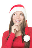 Santa woman thinking. Santa hat woman thinking and looking up isolated on white background. Close up of smiling Asian Caucasian female model wearing red Stock Image
