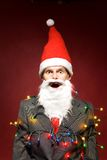 Santa wrapped in Christmas lights. Man in Santa Claus costume Royalty Free Stock Photos