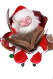 Santa writing in book. Closeup of Santa Claus (that jolly old elf that  lives at the North Pole) reading and writing in the book of good children, taken with a Royalty Free Stock Photos