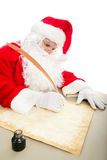 Santa Writing List on Parchment. Santa writing his Christmas list on parchment paper with a quill pen and ink stock image