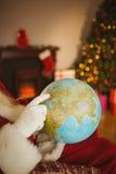 Santa wskazuje jego palcowego na kuli ziemskiej Zdjęcie Stock