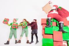 Santa& x27; s-hjälpredor som arbetar på nordpolen Honom som läser önskalistan Royaltyfri Bild