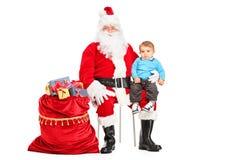 Santa y niño en su regazo que presenta al lado de un bolso Foto de archivo libre de regalías