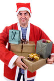 Santa. Young man with santa hat holding some gifts, isolated Royalty Free Stock Images