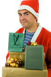 Santa. Young man with santa hat holding some gifts, isolated Stock Photography