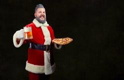 Santa z pizzą i szkłem piwo w jego rękach przy bożymi narodzeniami obraz royalty free