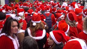 Santacon event in London. London, UK - December 2018 : Group of people dressed in santa outfits, holding and drinking alcoholic drinks while taking part in a stock footage