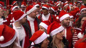 Santacon event in London. London, UK - December 2018 : Group of people dressed in santa outfits, holding and drinking alcoholic drinks while taking part in a stock video