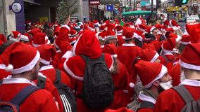 Santacon event in London. London, UK - December 2018 : Group of people dressed in santa outfits, holding and drinking alcoholic drinks while taking part in a stock video footage