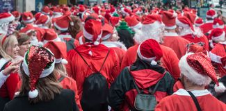 Santacon event in London. London, UK - December 2018 : Large crowd of people dressed in santa outfits, holding and drinking alcoholic drinks while taking part in royalty free stock photo