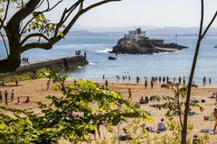 Santander, Cantabria, Spain. Santander, Spain. Views of the crowded Playa de los Peligros beach and the Isla de la Torre Tower Island royalty free stock photography