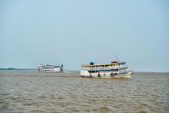 Santarem, Brazil - December 02, 2015: ships float on amazon river. Holiday ships on sunny blue sky. Summer vacation and wanderlust. Concept. Pleasure travel by stock photo