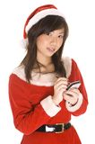 Santarina Makes Her List. A cute asian woman dressed in a santa outfit makes a list on a handheld computer stock photo