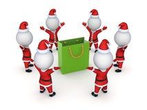 Santas around green packet. Stock Image