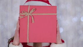 Santas assistant covered her face with a gift and looked out for him. Bokeh background. Close up stock video