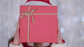 Santas assistant covered her face with a gift and looked out for him. Bokeh background. Close up . Slow motion stock footage