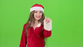 Santas assistant draws an airy congratulation on the new year. Green screen. Slow motion. Santas assistant in a red suit with her finger draws an airy stock video