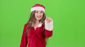 Santas assistant draws an airy congratulation on the new year. Green screen. Santas assistant in a red suit with her finger draws an airy congratulation on the stock footage