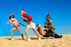 Santas atractivos que tiran de Santa en la playa Fotos de archivo