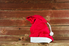 Santas cap at old weathered wooden background Stock Images