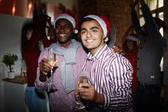 Santas with champagne. Two intercultural guys holding flutes with champagne while enjoying Christmas party Stock Photo