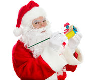 Santas Christmas Toy Shop. Santa painting a child's toy for Christmas. Isolated on white stock photos