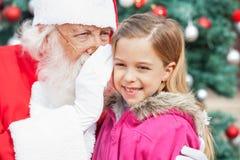 Santas Claus Whispering In Happy Girls öra Fotografering för Bildbyråer