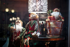 Santas and an Elf. Sitting in a shops window decorated for Christmas royalty free stock photos