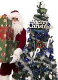 Santas gifts 5. Santa holding a few christmas presents for you near the christmas tree Stock Photo