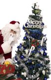 Santas gifts 7. Santa holding a few christmas presents for you near the christmas tree and telling you to be quiet Stock Photography