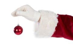 Santas hand is holding a Christmas bulb Stock Photos