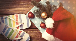 Santas hat and christmas bubbles with flip flops Royalty Free Stock Photography
