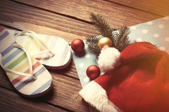 Santas hat and christmas bubbles with flip flops Stock Photo
